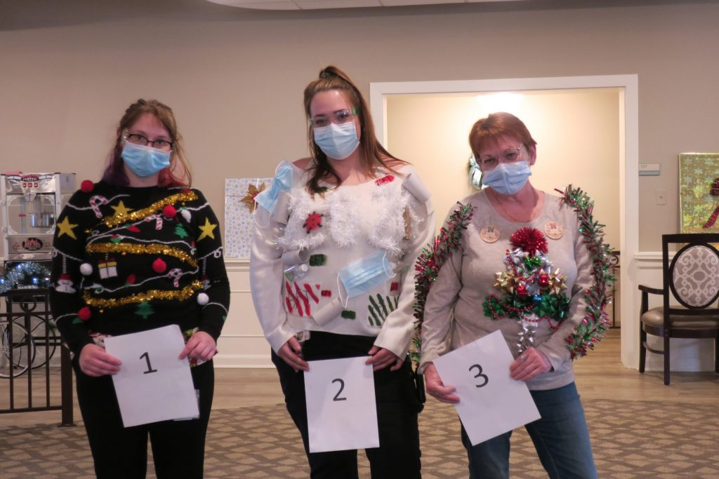 Three women wearing ugly Christmas sweaters and holding cards with numbers on them for judging.