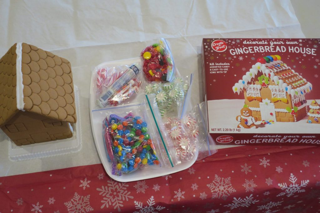 A decorate your own gingerbread house kit on a table with red and white tablecloth.