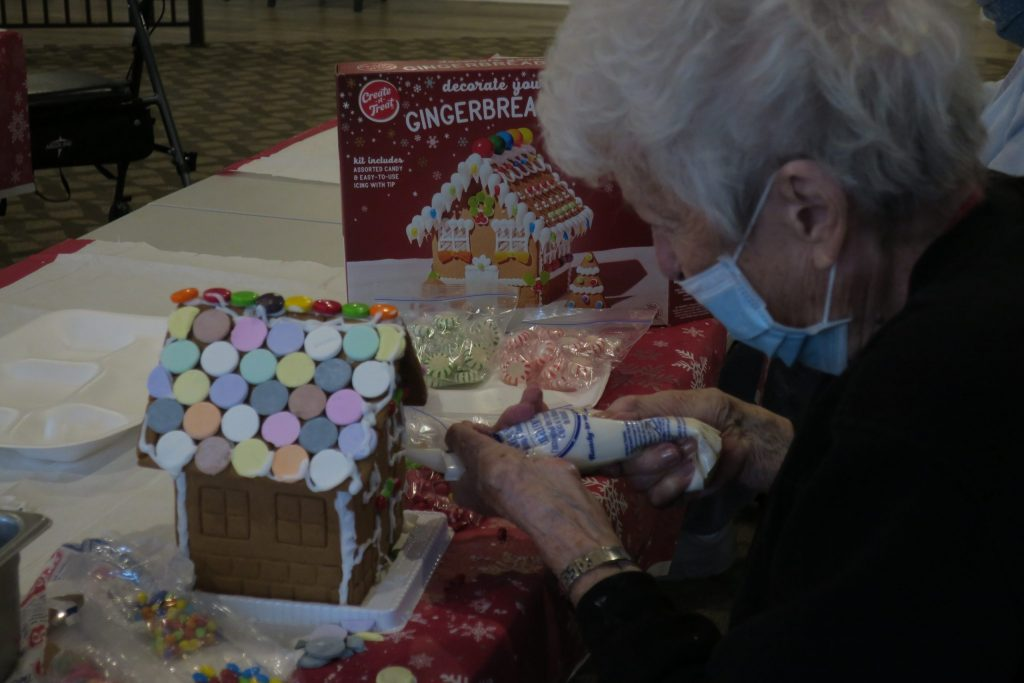 An elderly person with white hair spreads frosting on a gingerbread house.