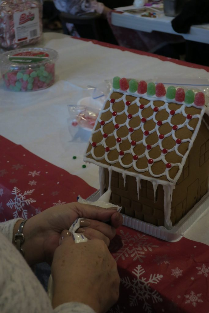 Someone spreads frosting on a gingerbread house.
