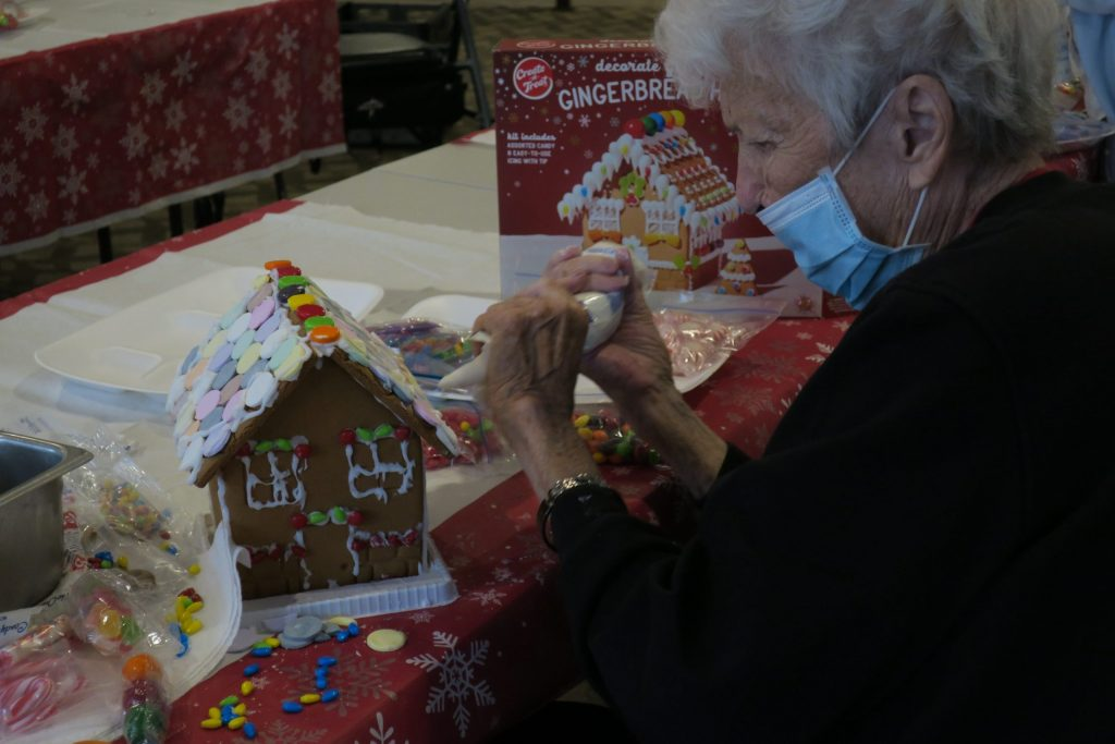 A masked elderly person works on a crumbling gingerbread house.