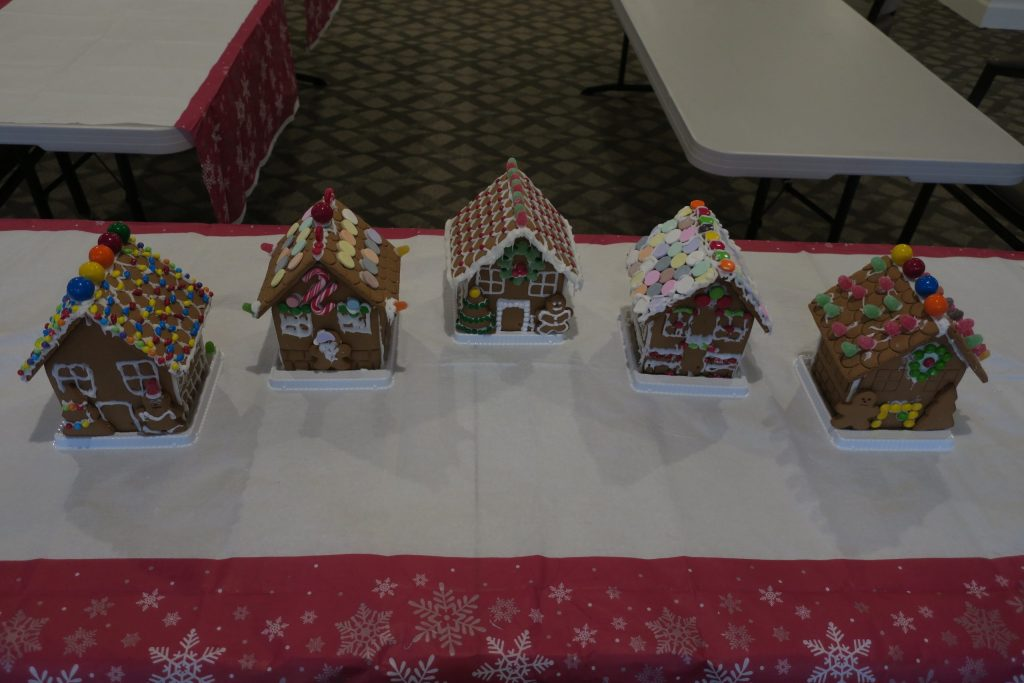 Five gingerbread houses on a table with red and white tablecloth.