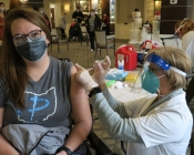A masked medical professional giving a masked patient her COVID-19 vaccine.