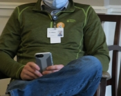 PPE masked man sitting and using his cell phone.