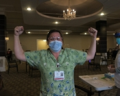 Masked woman raising two fists in victory after receiving the first dose of the COVID-19 vaccine!