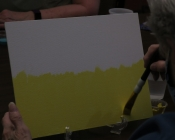 An elderly person paints yellow on a white canvas.