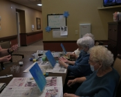 Three older women painting blues on three canvases at a table.