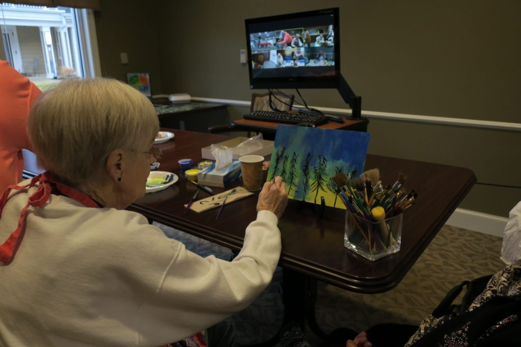 An elderly woman paints a lovely forest with blues, greens, and yellows.