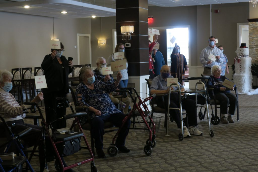 A room full of masked elderly people — many in walkers — gathered and sitting facing one direction.