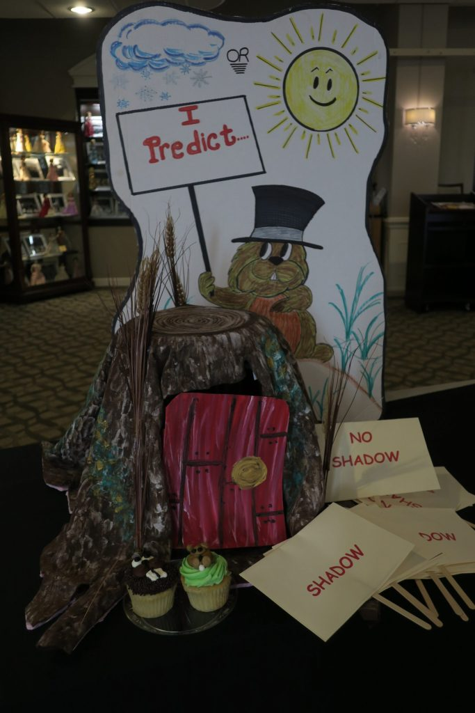 "A papier-mâché groundhog home in front of a white poster board cutout of a groundhog holding a sign that reads, ""I Predict."" The groundhog is surrounded by cards that say ""Shadow"" and ""No Shadow."""