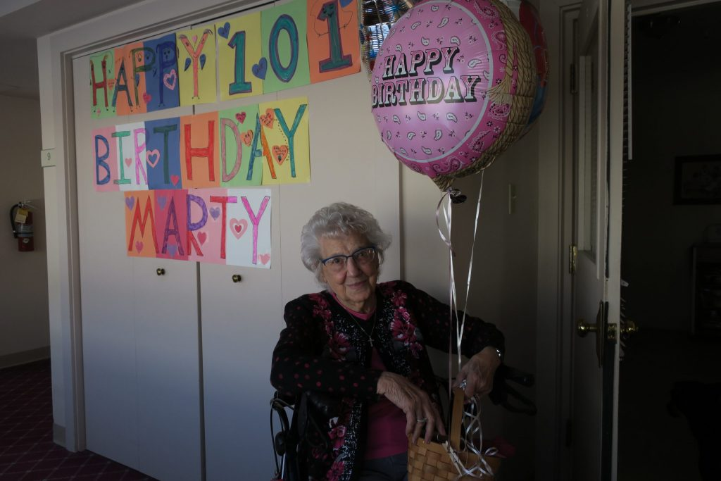 """A centenarian woman smiling and holding a pink """"Happy Birthday"""" balloon under a sign that says, """"Happy 101st Birthday Marty."""""""